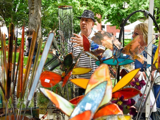 Mike Carlson, Cokato, shows some of his creations to a customer at a past Lemonade Art Fair.