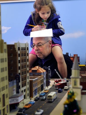Anna Ratliff, 6, uses her grandfather's scalp as a desk for checking-off listed items as part of a scavenger hunt for children Saturday. Jim Trietsch let his granddaughter ride his shoulders as they toured the Abilene Society of Model Railroaders' new home at 598 Westwood. As for Anna's pencil, his scalp survived unscathed.