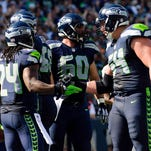 Seahawks running back Marshawn Lynch (24), offensive tackle Justin Britt (68), center Max Unger (60) and middle linebacker Bobby Wagner (54) celebrate after Lynch scored a touchdown against the Denver Broncos during the first half at CenturyLink Field.