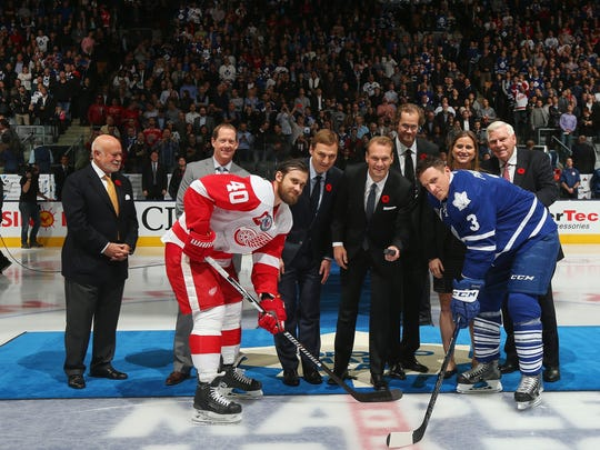 Peter Karmanos Jr., Phil Housley, Sergei Fedorov, Nicklas Lidstrom, Chris Pronger, Angela Ruggiero and Bill Hay drop the puck between Henrik Zetterberg #40 of the Detroit Red Wings and Dion Phaneuf #3 of the Toronto Maple Leafs prior to the game at the Air Canada Centre on November 6, 2015 in Toronto, Ontario, Canada.
