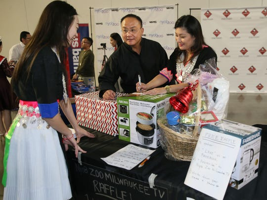 "Dawn Yang (right), general manager of the TV show ""Nyob Zoo Milwaukee,"" and her husband Thay Yang, CEO of WHMG Media, enter Lisa Vang of Appleton in a raffle during an event to promote the show at the Hmong New Year celebration at the State Fair Park Expo Center."
