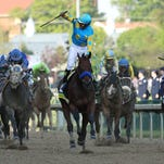 Victor Espinoza celebrates as he crosses the finish line on American Pharoah to win the Kentucky Derby.