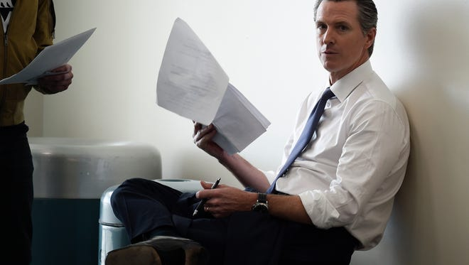 Democratic gubernatorial candidate Gavin Newsom looks over notes before speaking with delegates at the 2018 California Democrats State Convention Saturday, Feb. 24, 2018, in San Diego. (AP Photo/Denis Poroy)