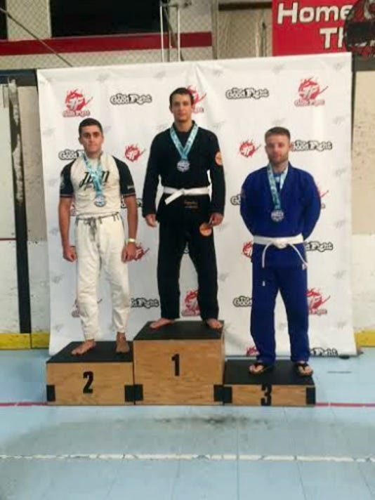 Christian Monterrey (middle) stands on the podium after taking gold in the gi grappling event at the Philadelphia Jiu Jitzu Challenge on July 11.