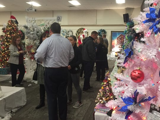 Dana Matz, director of the Zanesville-Muskingum County Chamber of Commerce, visits with bidders at the annual Festival of Trees on Friday.