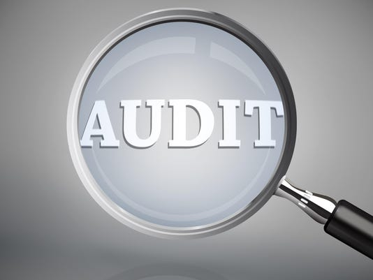 Magnifying glass showing audit word in white