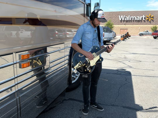 Anders Mouridsen practices playing his guitar in a Walmart parking lot in Hays, Kansas while touring.