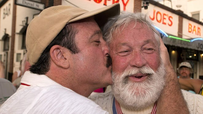 Wally Collins, the Phoenix man who won the Hemingway Days Look-Alike Contest, gets kissed by his son, Matt.