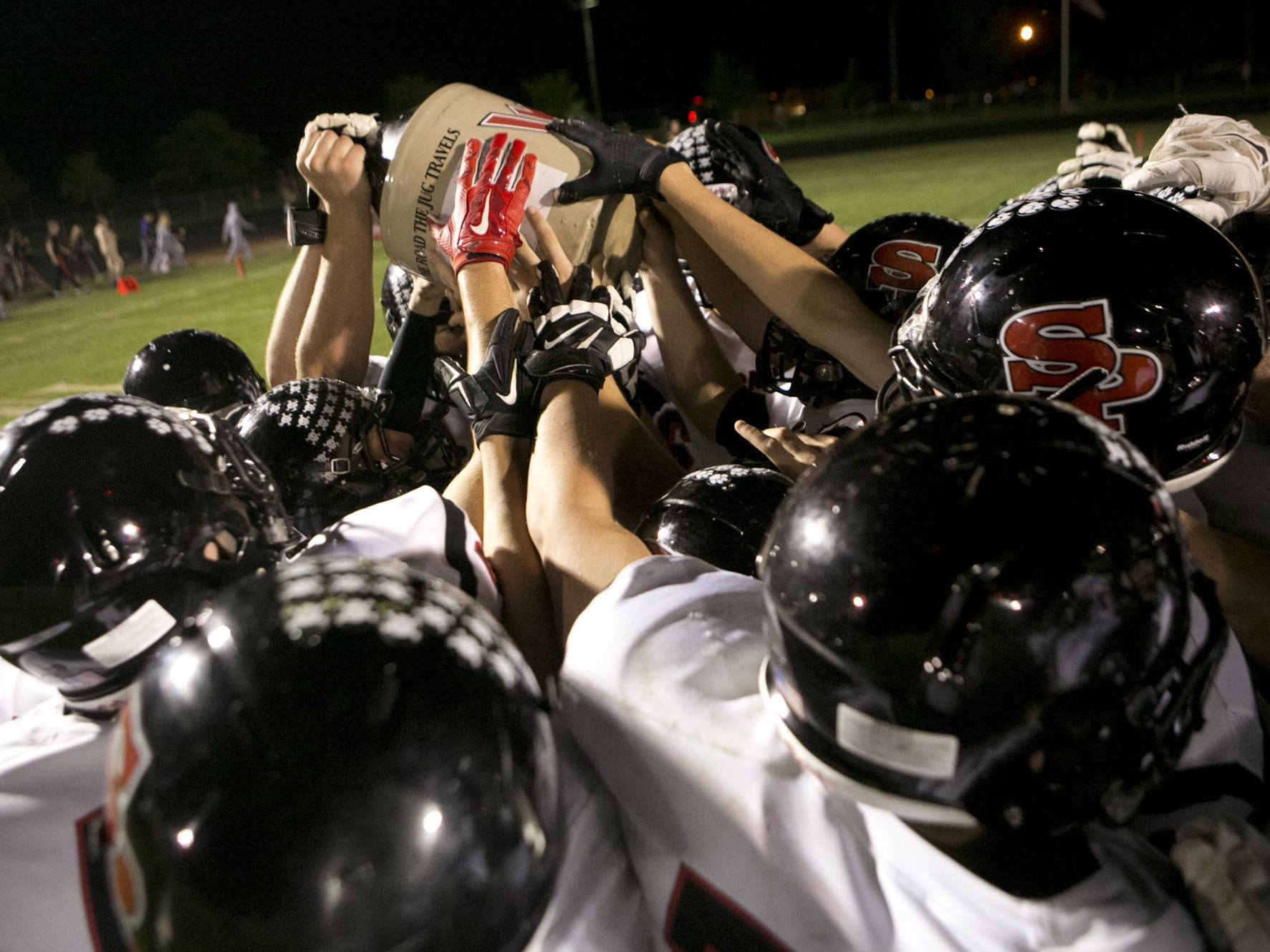 The SPASH football team lifts up the Old River Jug after defeating Wisconsin Rapids 38-14 in a Wisconsin Valley Conference football game at South Wood County Recreation Center in Wisconsin Rapids, Friday, Sept. 25, 2015.
