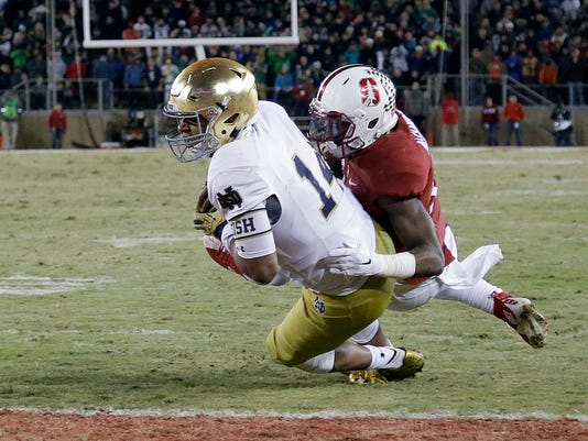 Notre Dame's DeShone Kizer (14) lunges into the end zone past Stanford cornerback Terrence Alexander for a 2-yard touchdown run late in the fourth quarter of an NCAA college football game Saturday, Nov. 28, 2015, in Stanford, Calif. Stanford won 38-36. (AP Photo/Marcio Jose Sanchez)