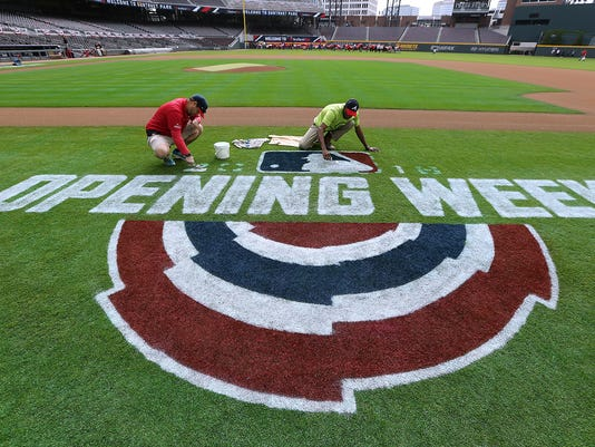 Members of the Atlanta Braves grounds crew put final touches on the field as the team prepares to play the Philadelphia Phillies in a home opening baseball game Thursday, March 29, 2018, in Atlanta. (Curtis Compton/Atlanta Journal-Constitution via AP)