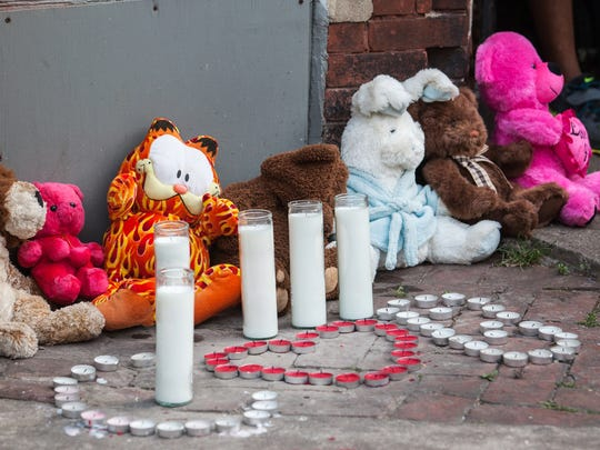 Stuffed animals and candles are on the ground outside a home in the 1000 block of Seventh Street at a vigil in July for Crystal Brown, an innocent bystander shot and killed July 6 as she walked out of a corner store at 7th and Adams streets.