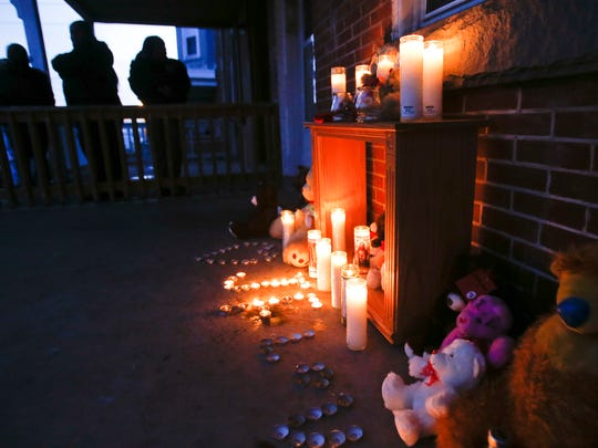 People gather at a memorial on the porch of a house on the 200 block of N. Broom Street.