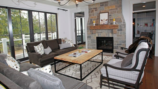 Reclaimed barn beams add interest to the ceiling, as does a two-sided lannon store fireplace with a mantel made of reclaimed wood in the family room. A deck can be accessed from the family room as well as the adjoining TV room.