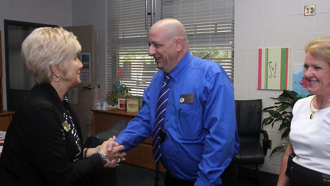 Steven LaTorre, center, shakes hands with Lee County School Board member Mary Fischer, as Caloosa Middle School principal Ann Cole stands nearby. LaTorre, a security guard at Caloosa Middle, was awarded Lee Schools' 2015 Educational Support Person of the Year.