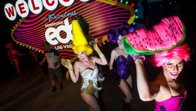 In this Saturday, May 19, 2018, photo, the Juicy Fruits, a group of costumed performers, make their way through the carnival square area during the second day of the Electric Daisy Carnival at the Las Vegas Motor Speedway in Las Vegas. Las Vegas Metro police say 35 people were arrested in the second day of the carnival, including 33 for drug-related felony charges.