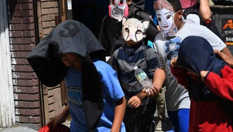 Children in masks shown as they were escorted out of the Cayuga Center in New York City's East Harlem neighborhood on June 21, 2018.