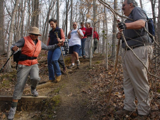 Mickey Luth holds back a fallen tree branch for Francis Ruffin, far left, and other fellow hikers on the Chickasaw Bluff trail at the Meeman Shelby Forest State Park.