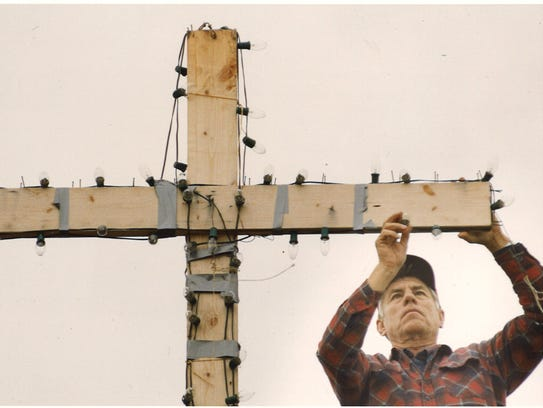 Bill Butts works on a lighted Christmas display in the shape of a cross on the top of his house Thursday, Dec. 9, 1993.