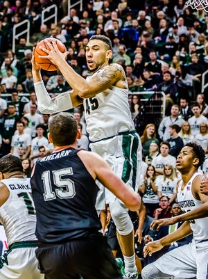 Denzel Valentine ,top, of MSU secures one of his 12 rebounds over Bobby Ahearn ,15, of Binghamton.  Valentine would contribute a double-double in the game.