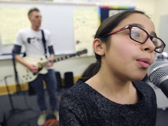 "Alejandra Llorente, 11, a sixth-grader at Evergreen Academy in Chicago, sings ""Counting Stars"" as Phil Jacobson plays guitar as part of the Chicago chapter of Guns over Guitars."