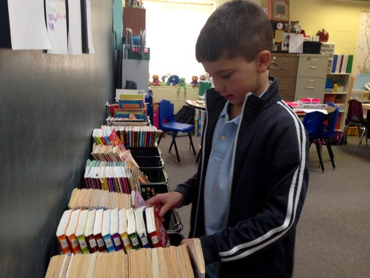 "South Grant Elementary third-grader Gavin Borland, 8, flips through the ""Diary of a Wimpy Kid"" book series in his new classroom on the first day of school Friday. Teachers have increased their classroom libraries and organized them by series and theme to mimic bookstores and encourage reading."