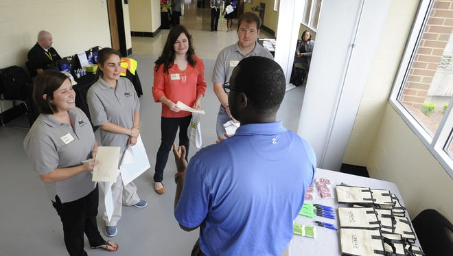 Employers talk at a booth during a job fair at Alabama State University. The bi-annual event has doubled in size.