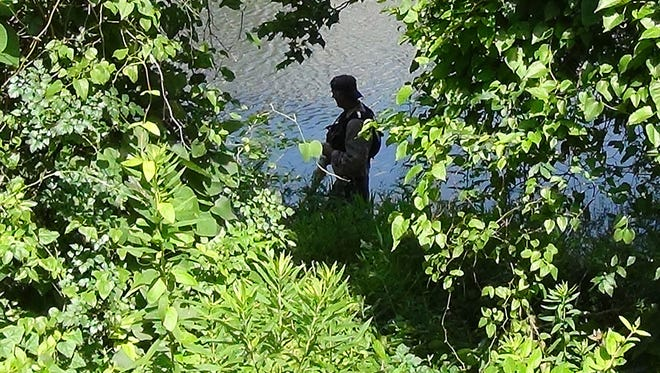 A member of the Mid-Mississippi strike team searches the area near Old River Place in Jackson where Jessica Hewitt's vehicle was found.