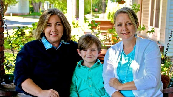 Cari Searcy, left, sits with partner Kimberly McKeand and their 8-year-old son Khaya at their home in Mobile. Searcy and McKeand, who married in California, sued the state after their attempt to have Searcy adopt Khaya was denied under Alabama's laws banning same-sex marriage. A federal judge Friday ruled in their favor, and declared the state ban unconstitutional. The state is appealing.