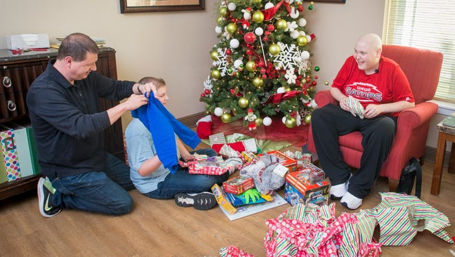 At right, Blake Mugridge, 17, laughs on Monday, Dec. 25, 2017, as his father, Mark Mugridge, opens someone else's present by mistake on Christmas morning at the Ronald McDonald House in Pensacola. The Mugridge family, of Wewahitchka, is staying at the Ronald McDonald House while Blake is undergoing treatment for leukemia.