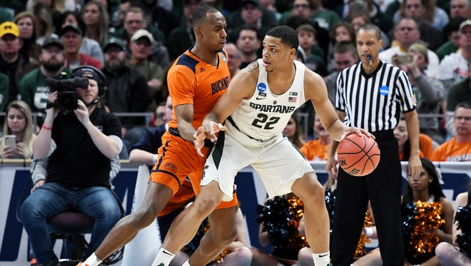 Michigan State's Miles Bridges, right, back into Bucknell's Nate Jones during the first half on Friday, March 16, 2018, at the Little Caesars Arena in Detroit.