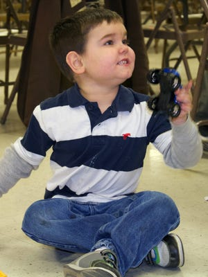 Garrett Shover plays with a cars and track toy set he received at a Hero's Fighting Cancer event at the New Franklin Fire Department on Dec. 20.