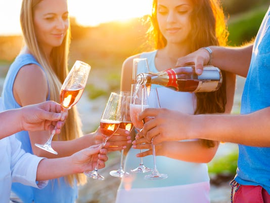 Happy friends pouring Rose`