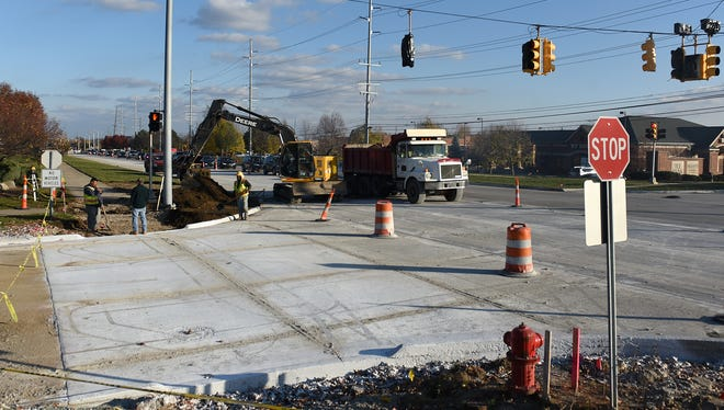 Workers finish up at an intersection just west of Haggerty Road on Six Mile on Nov. 16 as the route gets a major overhaul of its road surface.