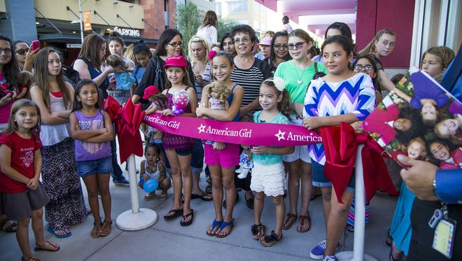 More than 1400 people had lined up to get tickets by 10 a.m. to enter the new American Girl doll store in the Scottsdale Quarter on Aug. 22.  Two Mesa sisters, Ella McTaggart, 9, (pink shorts, behind American Girl ribbon, holding doll, center) and Maggie McTaggart, 6, white skirt, were first in line.  Their grandmother, Alice Giehm of Phoenix got in line at 2 a.m.