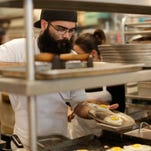 In this Friday, June 5, 2015 photo, sous chef Johnny Bacon places fried eggs on a plate while filling an order at Zak the Baker, in Miami. The Labor Department releases second-quarter productivity data on Wednesday, Sept. 2, 2015. (AP Photo/Lynne Sladky)