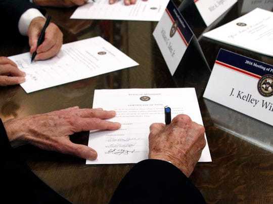 Members of the Mississippi Electoral College sign certificates of vote in the process of formally casting their electoral votes in Jackson, Miss., on Dec. 19, 2016.