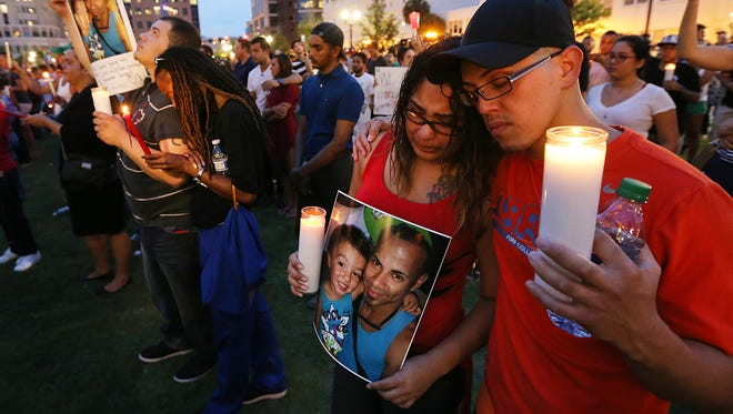 Frankie Arroyo, from left, Tonisha LaFayette, Tabbitha Segui and Jose Ramos hold candles and a photographs of their friend Xavier Emmanuel Serrano Rosado, who they said passed away today from his wounds, while thousands attend a vigil for family and friends that have lost loved ones in Orlando, Fla., Monday, June 13, 2016. A gunman killed dozens of people in a massacre at a crowded gay nightclub in Orlando on Sunday, making it the deadliest mass shooting in modern U.S. history.