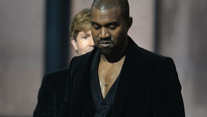 Beck is seen behind Kanye West after West made an unexpected appearance onstage during the 2015 Grammy Awards.