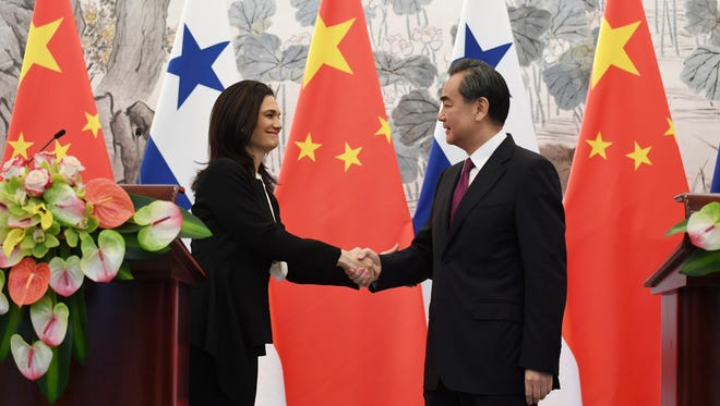 Panama's Foreign Minister Isabel de Saint Malo, left, shakes hands with her Chinese counterpart Wang Yi during a joint press briefing after signing a joint communique on establishing diplomatic relations, in Beijing Tuesday, June 13, 2017.