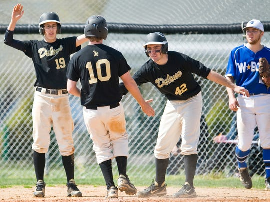 Delone Catholic's Joseph Ames (19) and Sam Stephen (42) greet Devon Craig at home plate Saturday vs. Waynesboro. Craig scored what turned out to be the winning run in a 2-1 victory vs. the Indians. (For the Evening Sun -- Jeff Lautenberger)