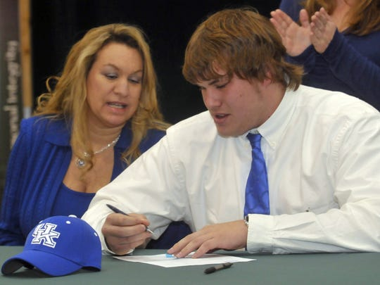 2-3-11, 1C  Catholic High School James Elliott, right, commits to play football for the University of Kentucky on National Signing Day, while his mother Pamela Dee Elliott, left, looks on.