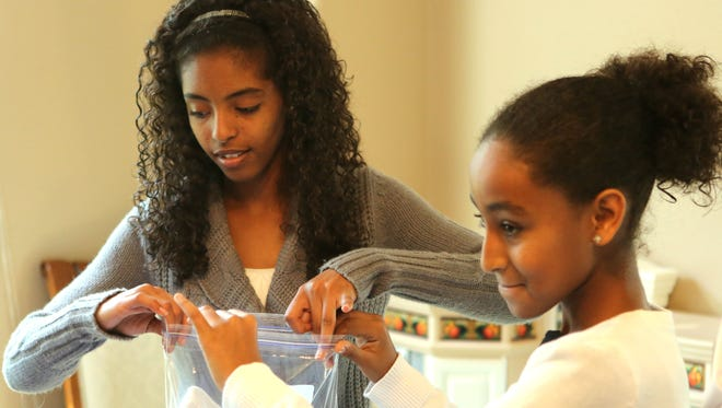 Kay, 15, left, and Ethiopia Wagner, 11, work together to make a kit. The Wagners put together 250-300 kits for homeless men that contain toiletries, socks and other necessities. The whole family goes to the Coalition for the Homeless on Christmas morning to hand out the kits and serve breakfast.