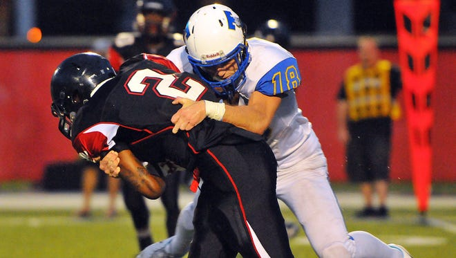 Titusville High's #18 Kyle Gullikson wraps up Palm Bay High's #2 Twonnie Pollard in the back field during Friday night at Palm Bay High stadium .