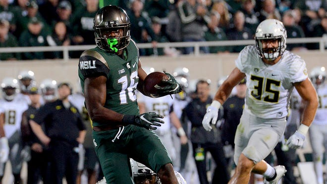 MSU's Aaron Burbridge looks to the end zone as he gets past an Oregon defender on his way to a second-quarter score at Spartan Stadium Saturday. Burbridge's eight catches Saturday were his most since 2012.