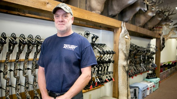 Owner Gary Hintz poses in front of bows for sale at
