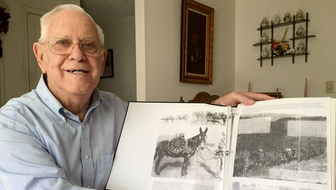 Art Naff shows his scrapbook from his service with the 613th Mule Pack Artillery during World War II. The Mule Pack wasn't just a colorful nickname.