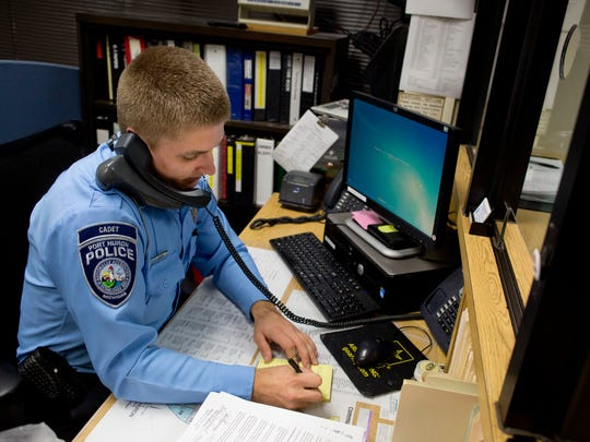 Port Huron Police Cadet Tyler Smith, of Fort Gratiot, takes a call while working at a reception desk Wednesday, Dec. 16, 2015 at the Port Huron Police Department. The department has received two $6,000 grants from the Community Foundation of St. Clair County to cover the cost of sending cadets to the police academy.