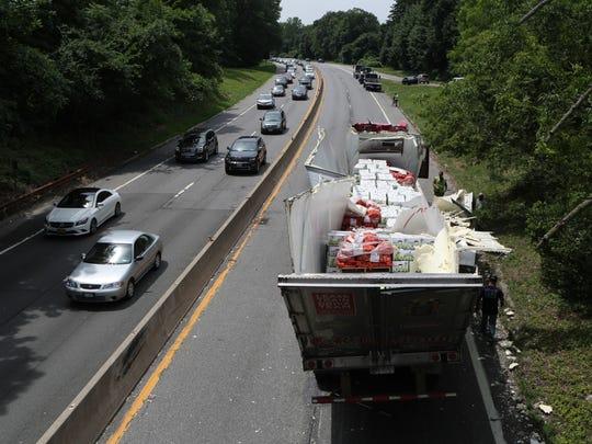 A tractor trailer carrying potatoes is split wide open