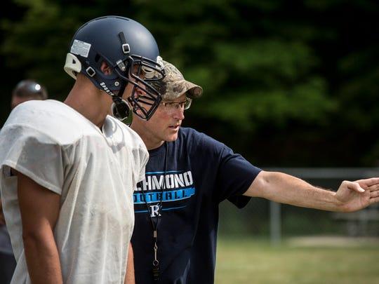 Coach John Kocher instructs Austin Sinda during football practice Thursday, August 11, 2016 at Richmond High School.